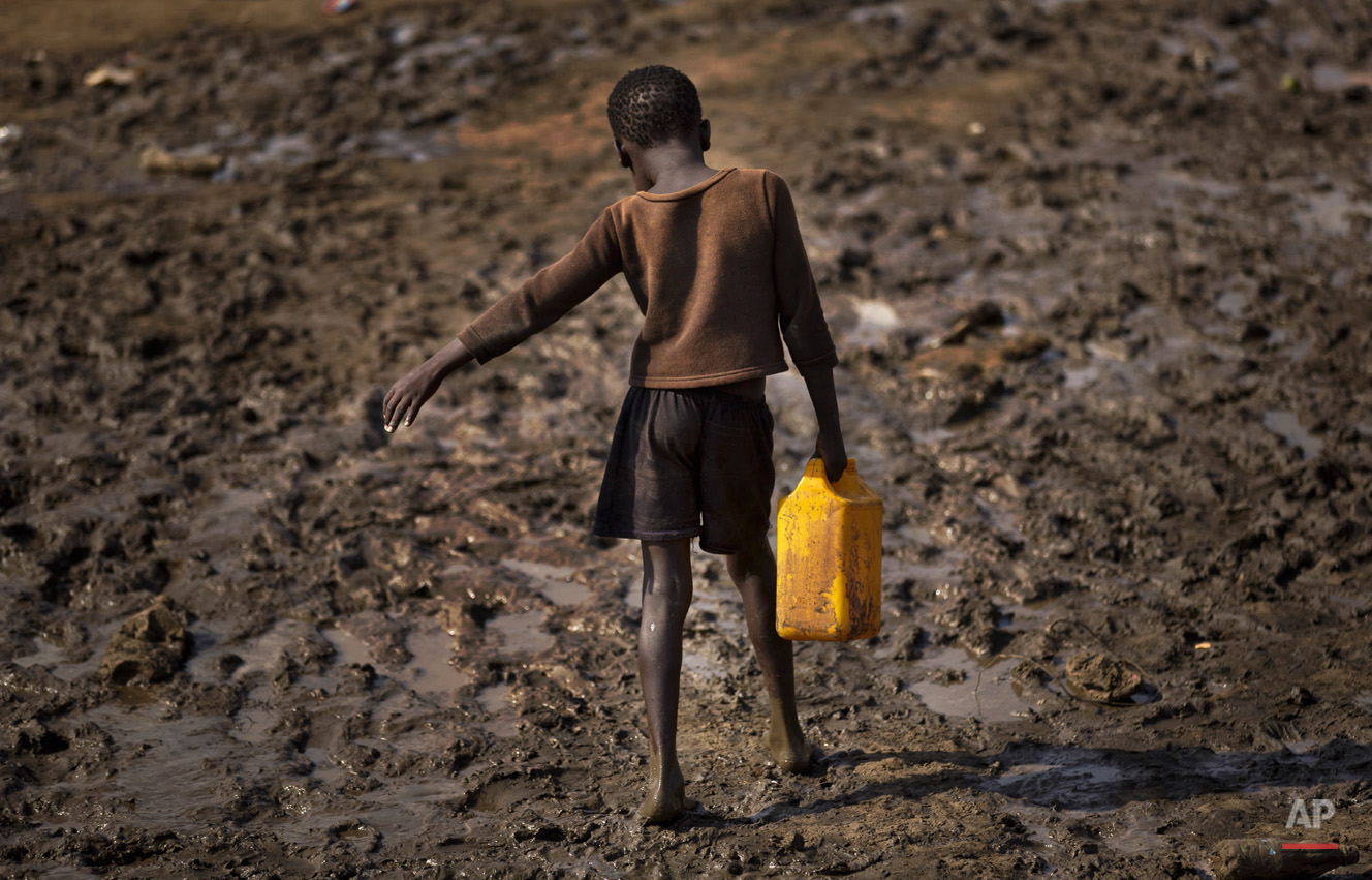 A displaced child struggles to carry a container of drinking water obtained from a truck across a slippery muddy patch of ground at a United Nations compound which has become home to thousands of people displaced by the recent fighting, in the capital Juba, South Sudan Sunday, Dec. 29, 2013. Some 25,000 people live in two hastily arranged camps for the internally displaced in Juba and nearly 40,000 are in camps elsewhere in the country, two weeks after violence broke out in the capital and a spiralling series of ethnically-based attacks coursed through the nation, killing at least 1,000 people. (AP Photo/Ben Curtis)