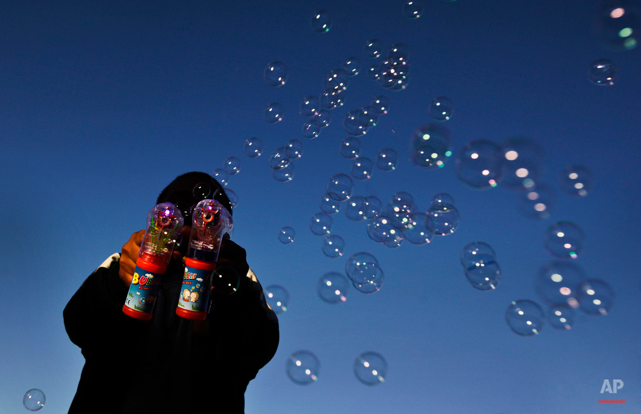 A man makes bubbles with two electric bubble-blowers at a day-long gathering of pro-Gadhafi soldiers and supporters, at dusk in Green Square, Tripoli, Libya Sunday, March 6, 2011. After unusually heavy gunfire erupted before dawn, thousands of Gadhafi's supporters poured into Tripoli's central square for a rally claimed by them to be a celebration of the regime taking back the cities of Ras Lanouf and Misrata - though both places remained in rebel hands late Sunday afternoon. (AP Photo/Ben Curtis)