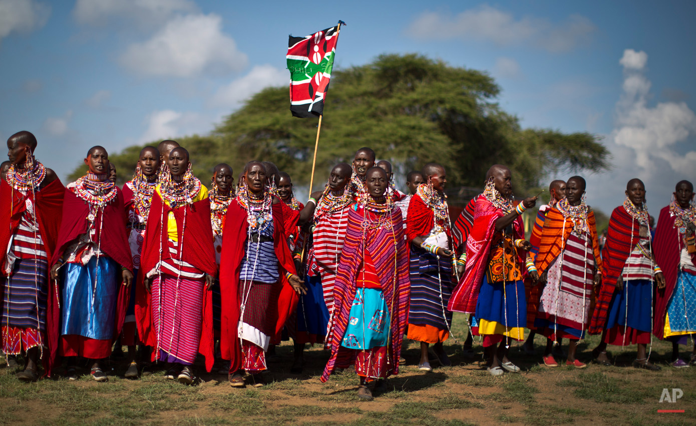 A group of Maasai women arrive to support the young warriors from their village at the annual Maasai Olympics in the Sidai Oleng Wildlife Sanctuary near to Mt Kilimanjaro, in southern Kenya Saturday, Dec. 13, 2014. Maasai men and women from the Amboseli and Tsavo region compete for medals and prizes in the event which aims for a sports competition of Maasai skills such as running, jumping, and throwing, to replace lion-hunting as the traditional warrior activity. (AP Photo/Ben Curtis)
