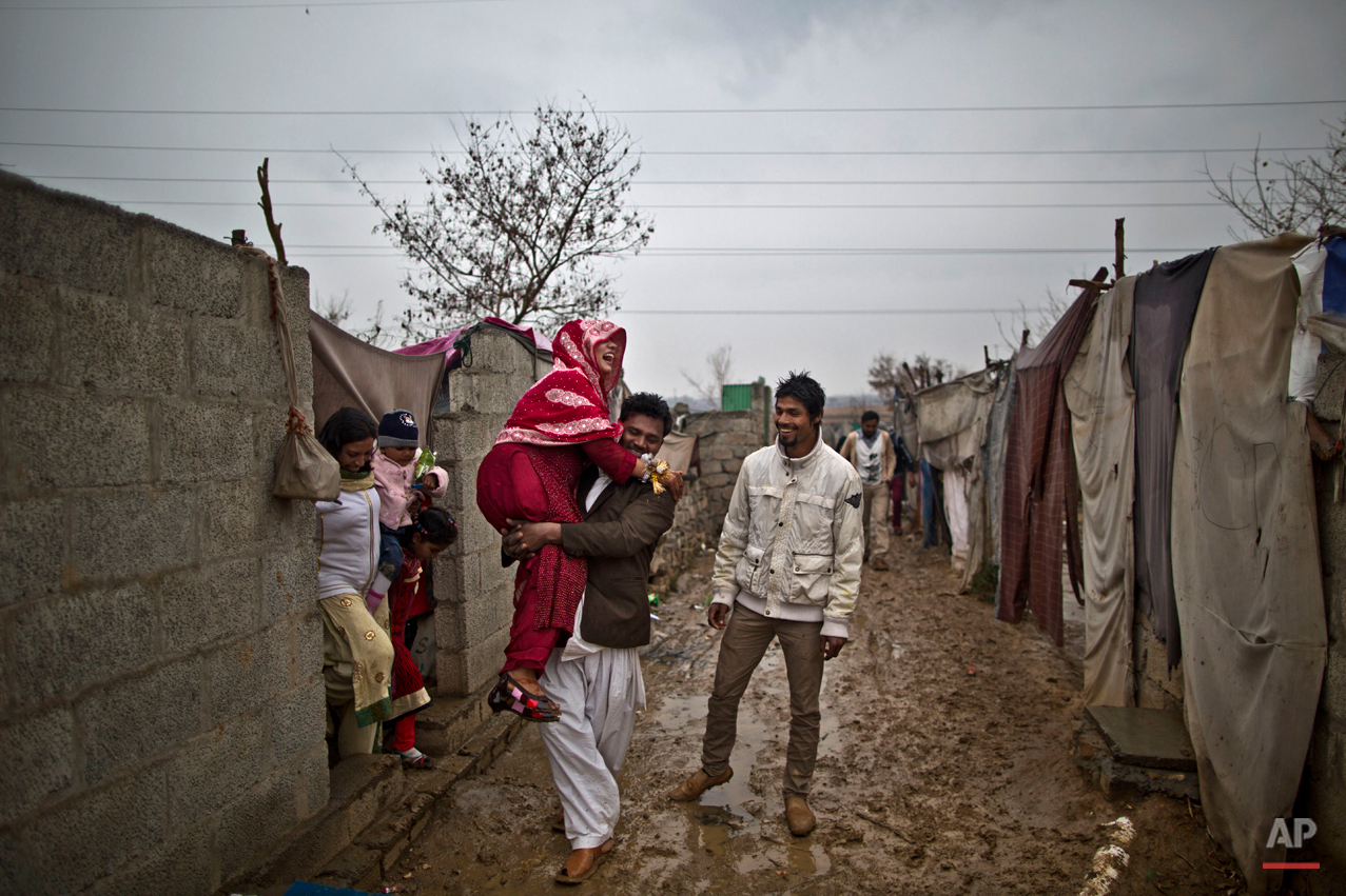 In this Saturday, Feb. 7, 2015 photo, Pakistani Christian bride Dunya Yacob, 24, is carried by her cousin to her groom's makeshift home to attend her wedding ceremony at a slum home to Christian families on the outskirts of Islamabad, Pakistan. ìSince I was a little girl, I dreamed of the day I would get married and put on a nice dress and have a nice party with a lot of people,î the 24 year old said. ìBut today, my dream didnít turn the way I imagined it, but there is nothing I can do about it. This is how our lives look like today and we have to adapt. (AP Photo/Muhammed Muheisen)