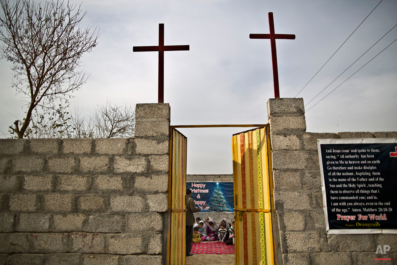 In this Friday, Feb. 6, 2015 photo, illiterate Pakistani Christians pray during a writing and reading class taught by a pastor and volunteers at a makeshift church in a slum on the outskirts of Islamabad, Pakistan. The Christian Colony just outside of Islamabad is home to many Christians who once lived in the capital, but fled in fear after a string of blasphemy allegations and killings. In this country of 180 million people, where Islam is the state religion and 95 percent of people are Muslims, Christians represent just a sliver of the population. (AP Photo/Muhammed Muheisen)