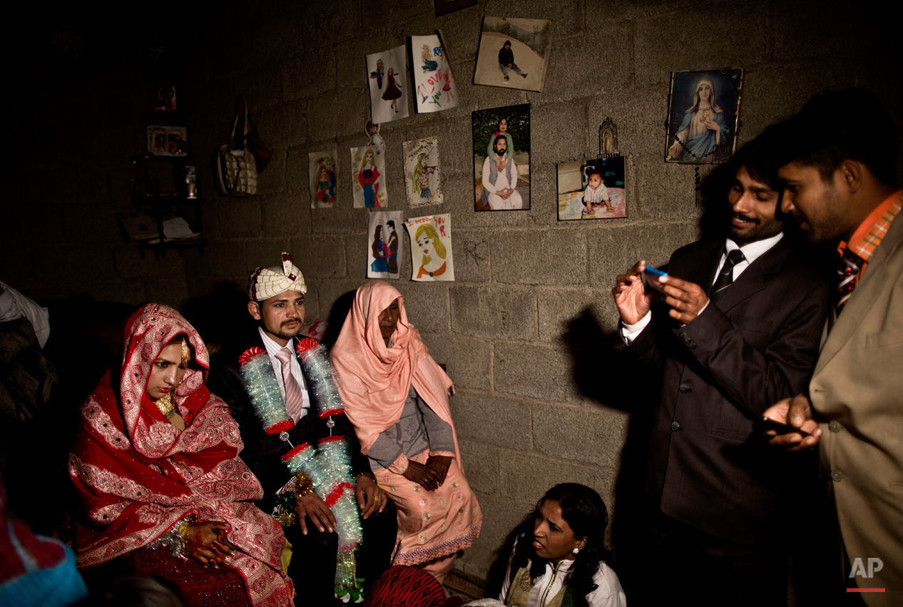 "In this Saturday, Feb. 7, 2015 photo, Pakistani Christian bride Dunya Yacob, 24, and her groom Indriaz Liaqat, 27, sit during their wedding ceremony in a makeshift home at a slum home to Christian families on the outskirts of Islamabad, Pakistan. ìSince I was a little girl, I dreamed of the day I would get married and put on a nice dress and have a nice party with a lot of people,î the 24 year old said. ""But today, my dream didn't turn the way I imagined it, but there is nothing I can do about it. This is how our lives look like today and we have to adapt."" (AP Photo/Muhammed Muheisen)"
