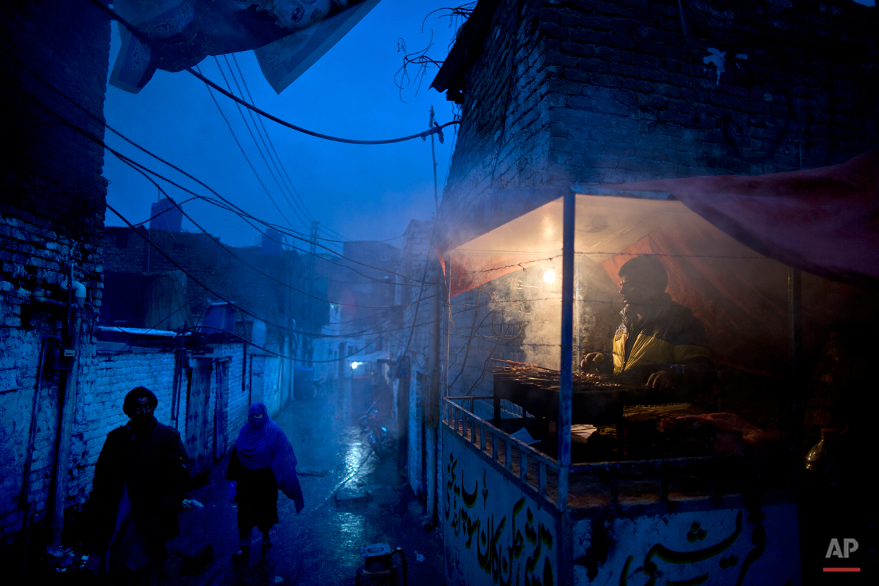 In this Monday, Feb. 2, 2015, photo, a Pakistani Christian vendor prepares meat on a grill to customers in a Christian neighborhood  in Islamabad, Pakistan. Most face daily discrimination and eke out a living by holding low-paying jobs, like street sweeping. However, theyíve carved out their own lives in a country that faces near-daily attacks by Islamic extremists. (AP Photo/Muhammed Muheisen)