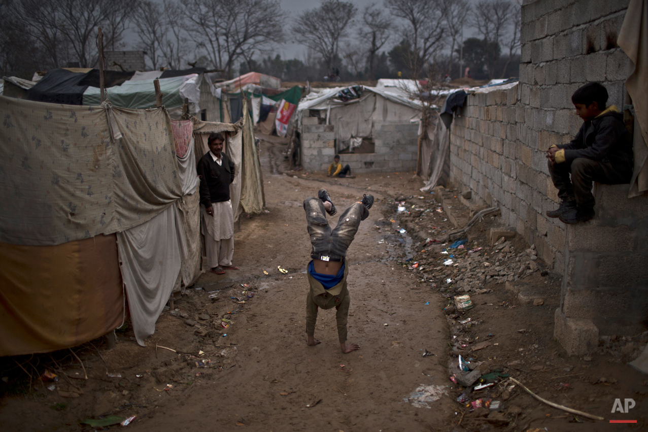 In this Saturday, Feb. 7, 2015 photo, Pakistani Christian children play in a slum home to Christian families on the outskirts of Islamabad, Pakistan. This slum on the outskirts of Pakistanís capital looks like many others ringing it, with dirt roads and cement-block homes, until a passer-by sees a simple black banner bearing a Bible verse about Jesus Christís resurrection. (AP Photo/Muhammed Muheisen)