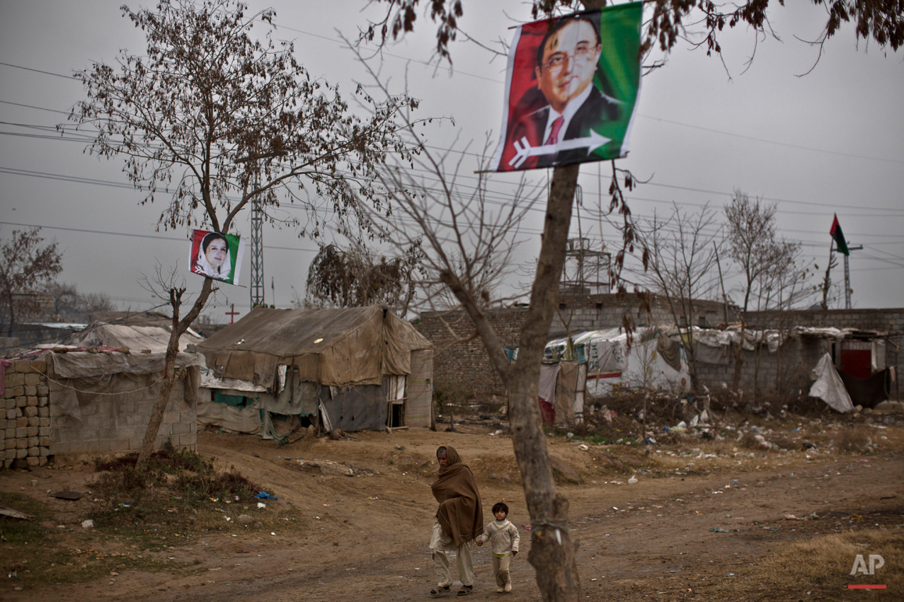 In this Saturday, Feb. 7, 2015 photo, banners show Former Pakistani President Asif Ali Zardari, top right, and his late wife, former Prime Minister Benazir Bhutto, as an elderly Christian man holds his grandson's hand at a slum home to Christian families on the outskirts of Islamabad, Pakistan. The Christian Colony is home to many Christians who once lived in the capital, but fled in fear after a string of blasphemy allegations and killings. In this country of 180 million people, where Islam is the state religion and 95 percent of people are Muslims, Christians represent just a sliver of the population. (AP Photo/Muhammed Muheisen)