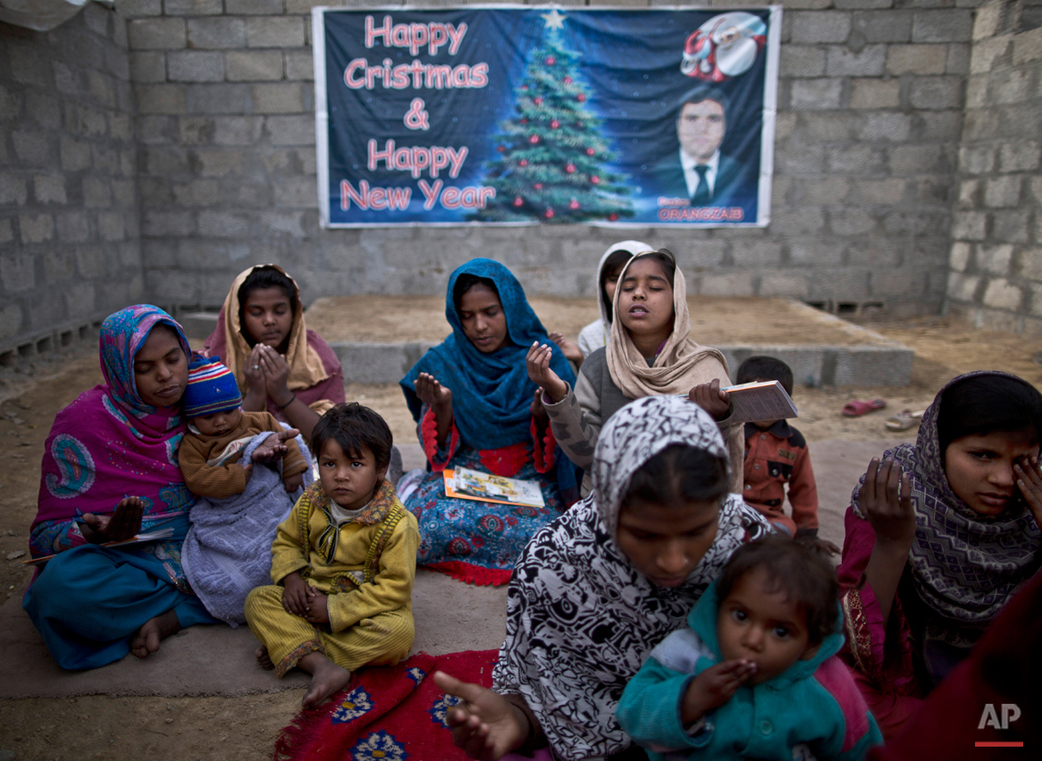 In this Friday, Feb. 6, 2015 photo, Pakistani Christians pray before starting class at a makeshift church in a slum home to Christian families on the outskirts of Islamabad, Pakistan. Most Christians face daily discrimination and eke out a living by holding low-paying jobs, like street sweeping. However, theyíve carved out their own lives in a country that faces near-daily attacks by Islamic extremists (AP Photo/Muhammed Muheisen)