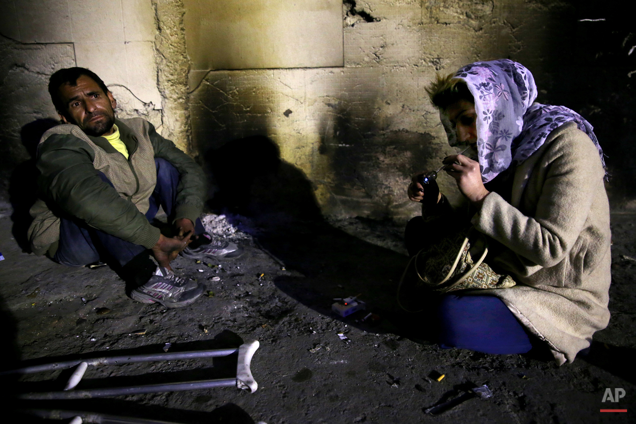 In this Wednesday, Feb. 4, 2015 photo, a female addict uses crystal meth in a street in midnight in Tehran, Iran. Anti-narcotics and medical officials say more than 2.2 million of Iran's 80 million citizens already are addicted to illegal drugs, including 1.3 million on registered treatment programs. They say the numbers keep rising annually, even though use of the death penalty against convicted smugglers has increased, too, and now accounts for more than nine of every 10 executions. (AP Photo/Ebrahim Noroozi)