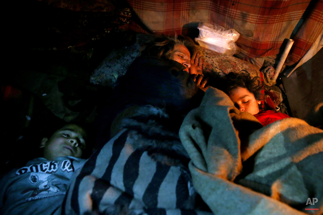 In this Wednesday, Feb. 11, 2015 photo, a female drug addict sleeps with her children at their make-shift shelter in a suburb of Tehran, Iran. Anti-narcotics and medical officials say more than 2.2 million of Iran's 80 million citizens already are addicted to illegal drugs, including 1.3 million on registered treatment programs. (AP Photo/Ebrahim Noroozi)