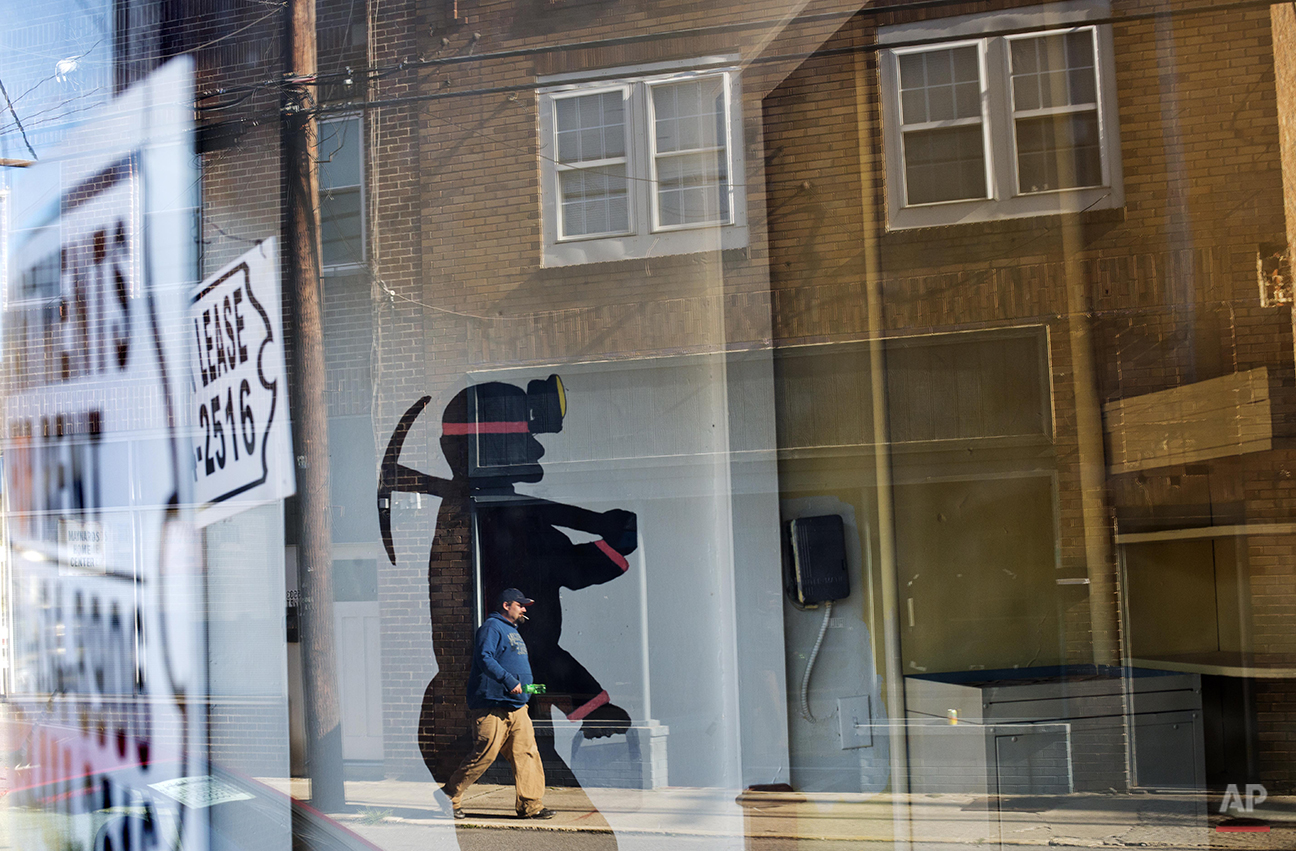 In this Oct. 17, 2014 photo, a mural of a coal miner stands in an empty storefront as signs advertising vacant apartments and stores hang in the windows along the main business street in Cumberland, Ky. Harlan County's population has shrunk along with the coal industry, to around 28,000, its lowest since 1920. (AP Photo/David Goldman)