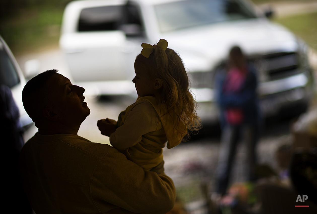 "In this Oct. 20, 2014 photo, After spending the weekend at home Scottie Sizemore says goodbye to his daughter Rylan, 3, as he leaves to return to his job working at a coal mine some five hours away in the western part of the state, in Harlan, Ky. After Sizemore's company announced they were slashing salaries 7 and a half percent and not long after that another 7 percent cut was coming, he decided to leave the mountains his family has called home for at least four generations and take a job coal mining in Western Kentucky. Since commuting home on weekends, Sizemore is hoping to pack up their home in Harlan and have the family back under one roof out west. ""She has really hard time with it,"" said Sizemore. (AP Photo/David Goldman)"