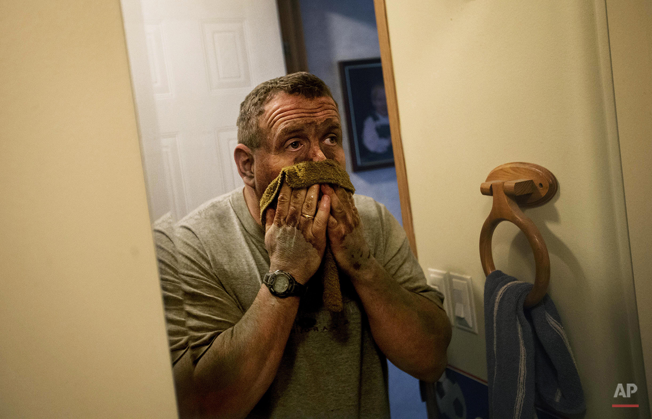 "In this Oct. 20, 2014 photo, third generation coal miner Keith Johnson washes coal dust off his face in his bathroom as he arrives home after working the graveyard shift underground in a coal mine in Evarts, Ky. Johnson, 43, is paying on a $20,000 hospital bill incurred while working at a company that offered no insurance. He's spent about $40,000 from his retirement fund to stay in Harlan. ""A few years ago, I would have said we had it made and we was gong to live a long life and retire here. But it's dim right now,"" says Johnson. ""There's no jobs, and what jobs are there are dwindling out. It's a bleak outlook for sure for the coalfields in eastern Kentucky."" (AP Photo/David Goldman)"