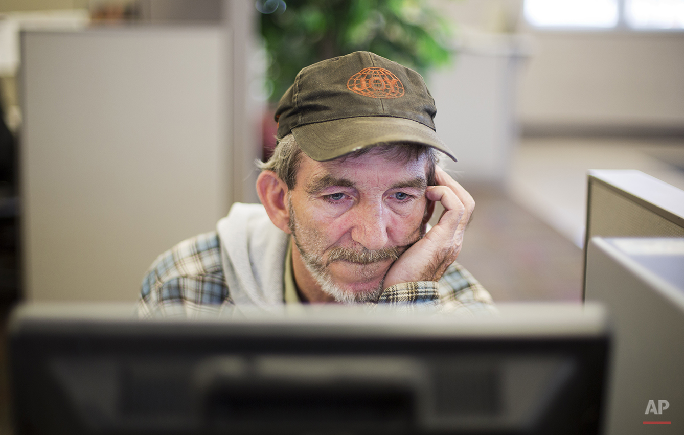 "In this Oct. 20, 2014 photo, unemployed coal miner Eddie Jones looks for jobs on a computer at the Kentucky Career Center in Harlan, Ky. With no computer at home, he goes to the employment office two or three times a week to see what's available. In the meantime, Jones has been making do with odd jobs, painting, digging ditches, mowing grass. ""Just something to pick up 40 or 50 bucks to pay a water bill,"" he says. Jones was on unemployment for 26 weeks. He is angry that Congress failed to pass an extension. ""They've bailed out every entity in the country,"" he says. ""The banking industry. The airline industry. The car industry. Everybody but the American worker."" (AP Photo/David Goldman)"