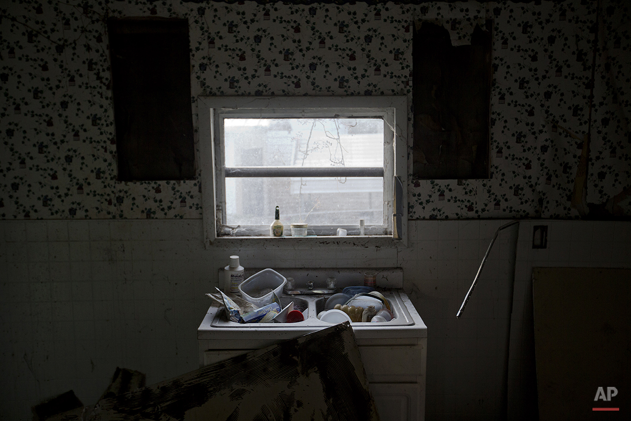 In this Oct. 17, 2014 photo, dishes and garbage sit in a kitchen sink in an abandoned home near coal mines no longer in use in Lynch, Ky. The community of Lynch, built as a company town in 1917 by U.S. Coal and Coke, a subsidiary of U.S. Steel, was at the time the largest coal camp in the world. It was built to house the many workers and their families mining the coal to be used by U.S. Steel. The population peaked to around 10,000 but has since diminished to roughly 747 according to a 2010 census. U.S. Steel started to sell the houses to the residents as it looked to move its coal production to a newer plant in Corbin, Ky., in 1955. Coal production decreased over the years as the use of oil and natural gas increased and the progression of less labor intensive coal mining techniques meant fewer employees needed. With coal as the sole major industry in the area, population numbers dropped as people left to look for work elsewhere. The homes now sit abandoned up the street from the old mines that have since been turned into a museum. (AP Photo/David Goldman)