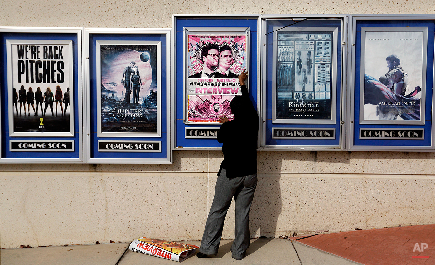 """A poster for the movie """"The Interview"""" is taken down by a worker after being pulled from a display case at a Carmike Cinemas movie theater, Wednesday, Dec. 17, 2014, in Atlanta. Georgia-based Carmike Cinemas has decided to cancel its planned showings of """"The Interview"""" in the wake of threats against theatergoers by the Sony hackers. (AP Photo/David Goldman)"""