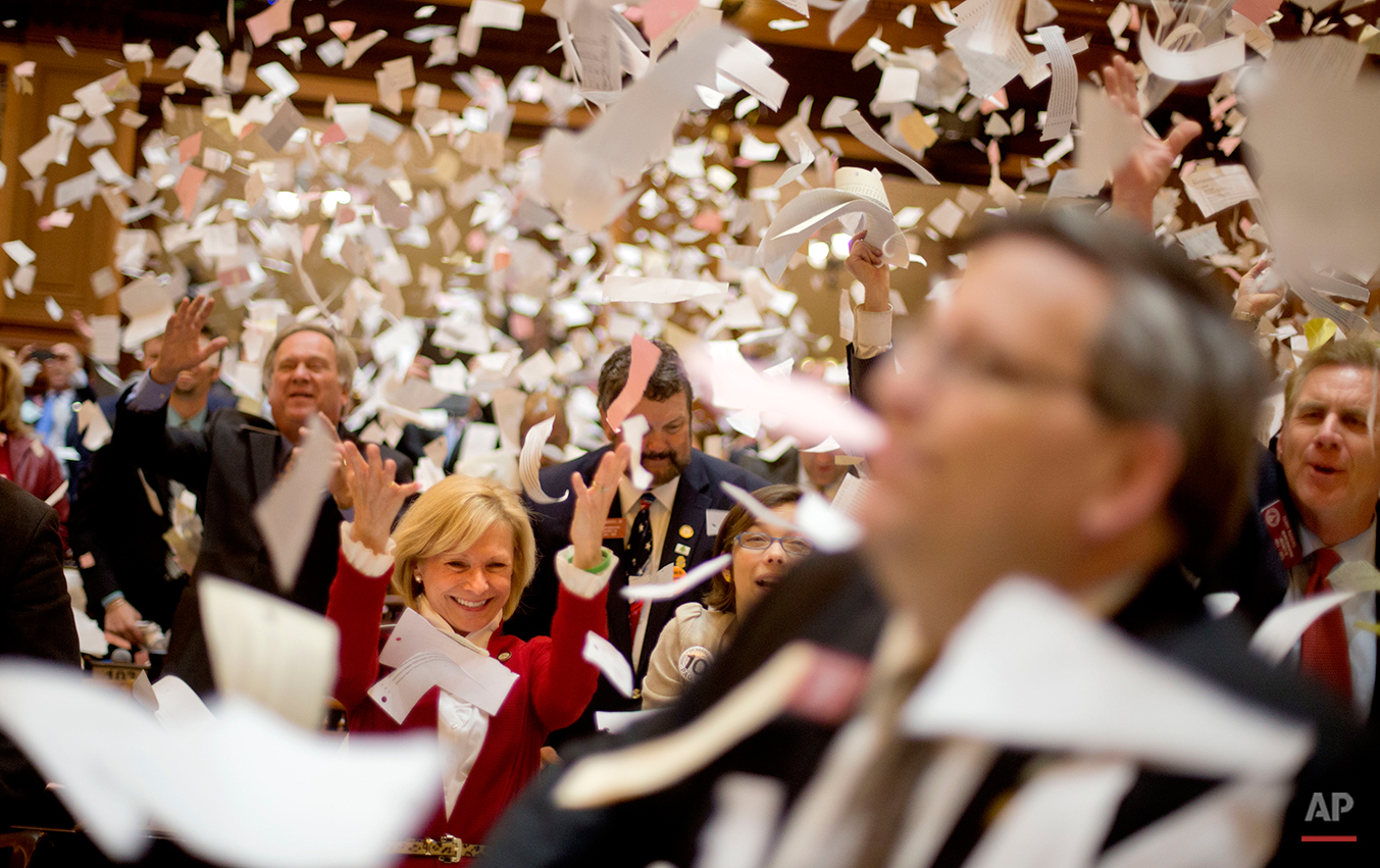 Georgia Rep. Katie Dempsey, R-Rome, left, throws up paper from her desk with fellow lawmakers at the conclusion of the legislative session in the House chamber, Thursday, March 28, 2013, in Atlanta. (AP Photo/David Goldman)