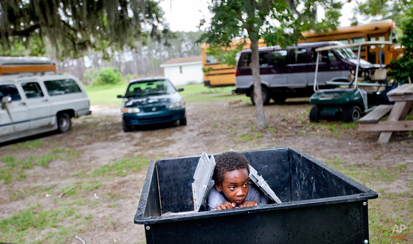 Jermarkest Wilson, 7, plays in a cart in the backyard of his home on Sapelo Island, Ga. on Sunday, June 9, 2013. Eight children catch a ferry every morning to attend school on the mainland since the last school operating on the island closed in 1978. (AP Photo/David Goldman)