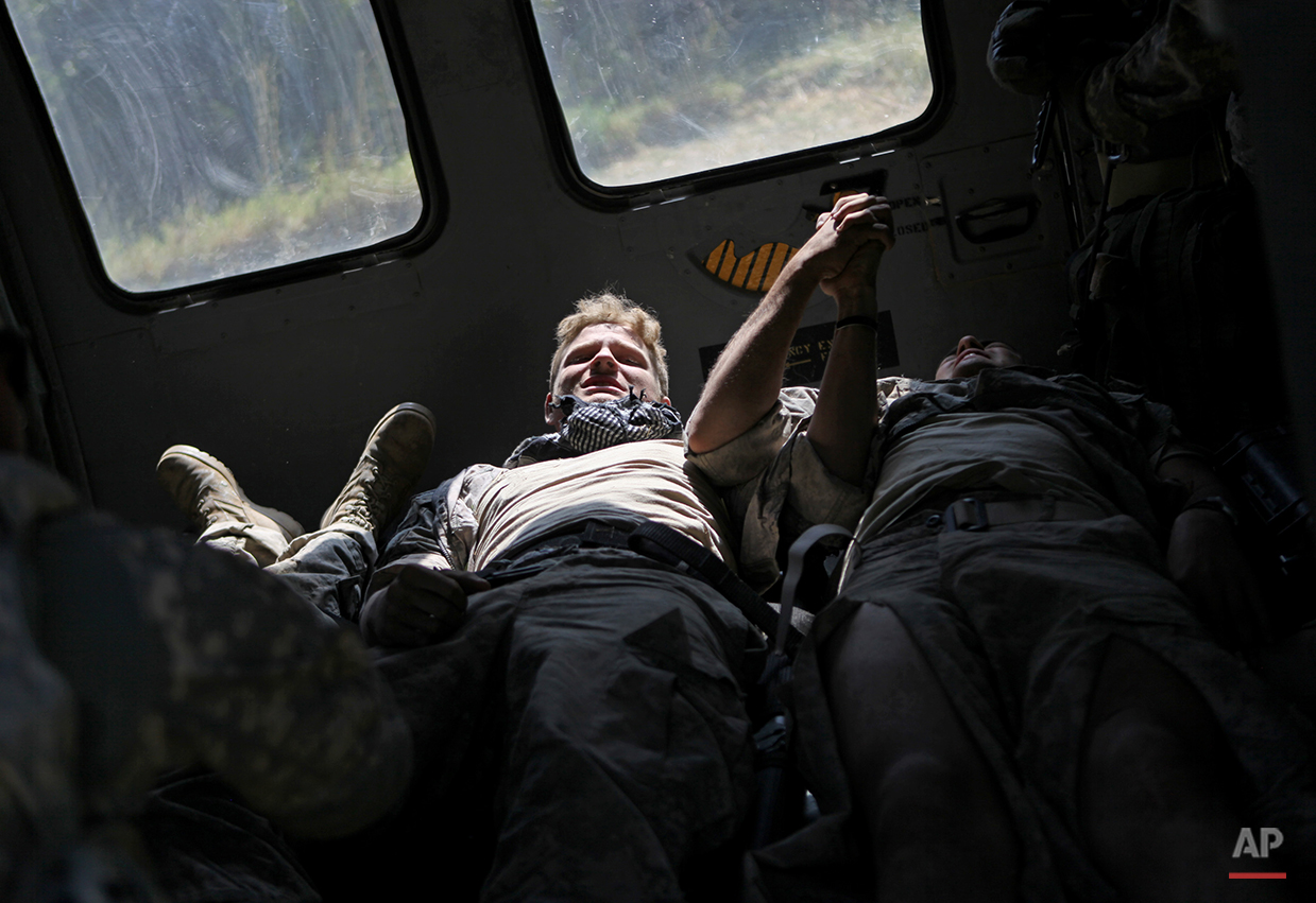 Wounded U.S. Army soldiers Spc. Kenneth Dykes, 20, left, of Greenville Tenn., and Pfc. James Gordon, 20, of Texas U.S. soldiers of the U.S. Army's Apache Company 2nd Battalion 87th Infantry Regiment, part of the 3rd Combat Brigade 10th Mountain Division based out of Fort Drum, N.Y., grab each other's hands after being loaded side by side into a medi-vac helicopter after their armored vehicle hit an improvised explosive device in the Tangi Valley of Afghanistan's Wardak Province Wednesday Aug.19, 2009. (AP Photo/David Goldman)