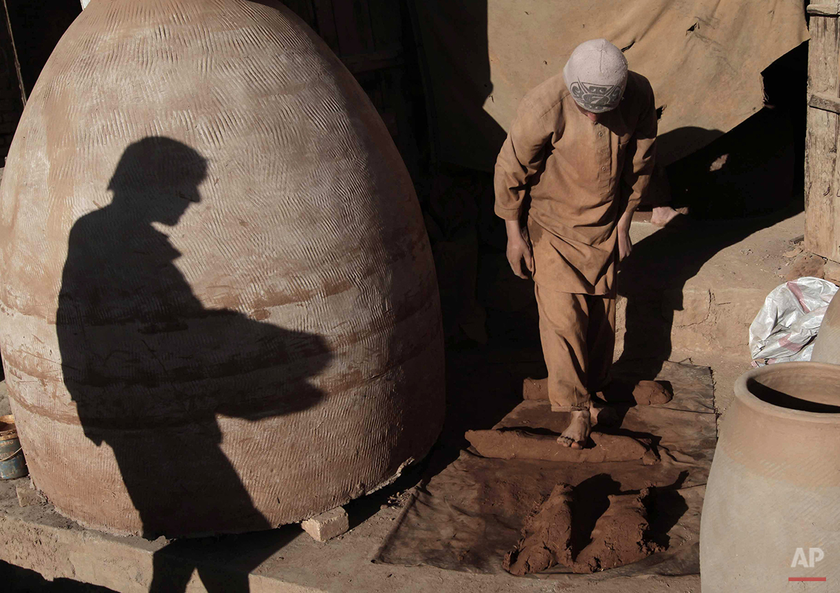 An Afghan potter works on his pottery at his shop in Kabul, Afghanistan, Thursday, Dec. 19, 2013. The potter makes about 800 Afghani ($14) per day. (AP Photo/Rahmat Gul)