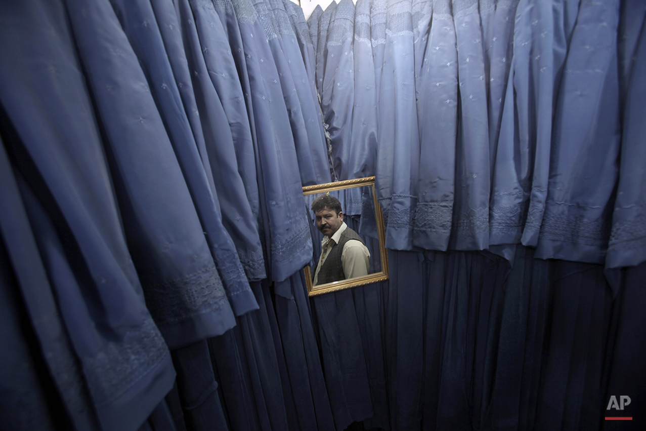 In this Saturday, Oct. 29, 2011 photo, shop owner Chppar Abdulsattar, 42, is reflected in a mirror inside his Burqa shop in Kabul, Afghanistan. (AP Photo/Muhammed Muheisen)