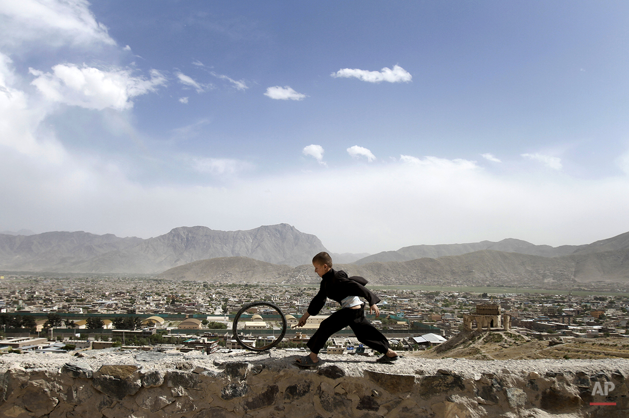 An Afghan boy pushes a wheel on the Naderkhan hill in Kabul, Afghanistan, Wednesday, May, 30, 2012. (AP Photo/ Ahmad Jamshid)