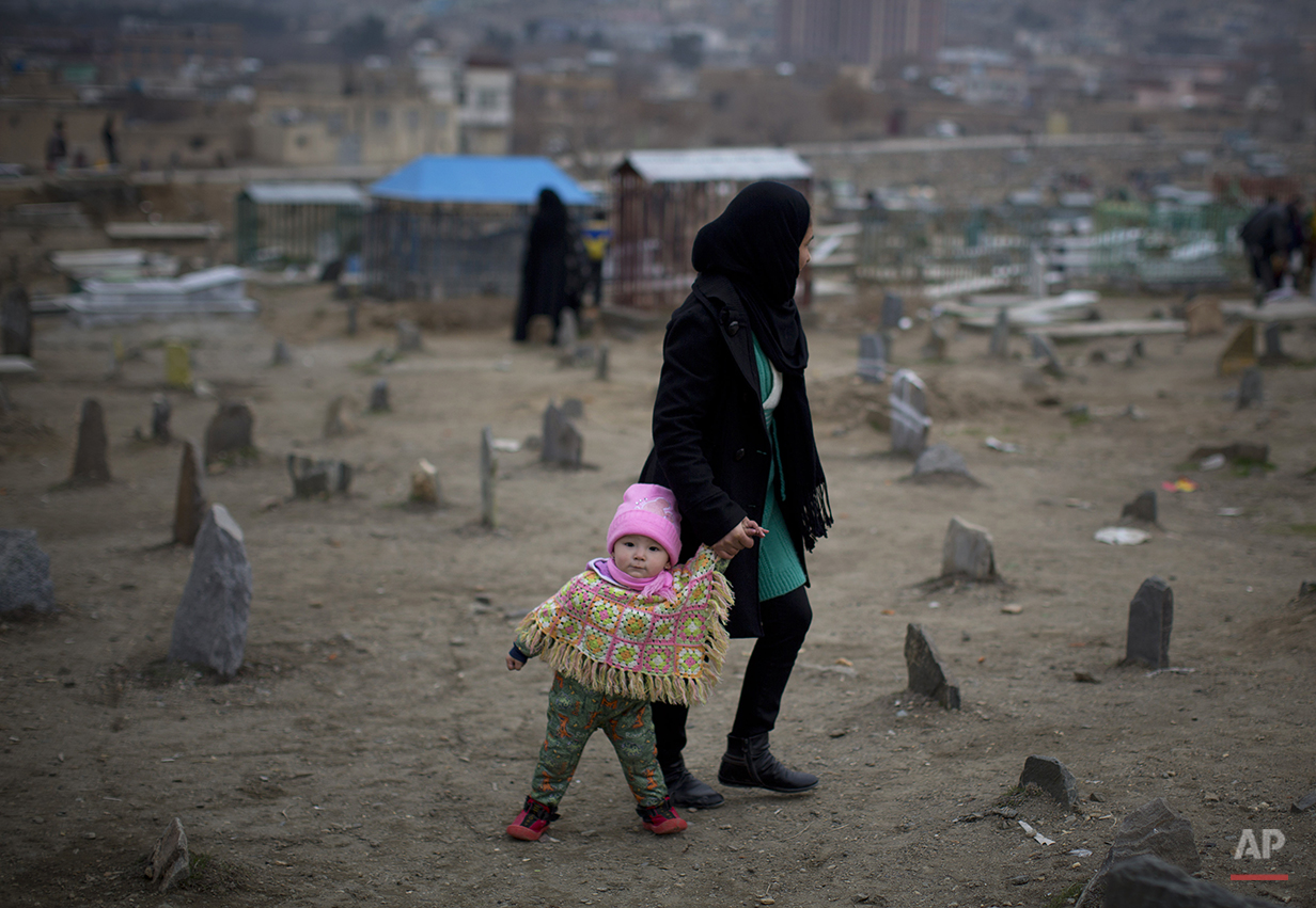 An Afghan woman walks with her little daughter across a cemetery in the center of Kabul, Afghanistan, Friday, March 7, 2014. On the eve of the International Women's Day 2014, Afghanistan has been named the worst place in the world to be a woman, according to Amnesty International. (AP Photo/Anja Niedringhaus)