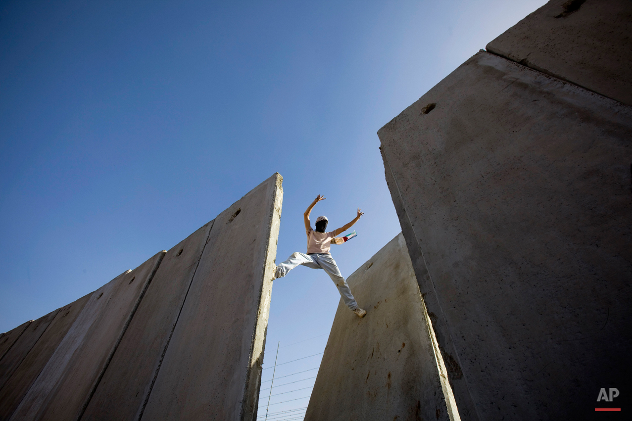 A Palestinian demonstrator gestures atop the separation barrier, moments after knocking down a segment of the concrete wall, during a protest against the barrier in the West Bank village of Nilin, near Ramallah, Friday, Nov. 6, 2009. Palestinian President Mahmoud Abbas said Thursday he does not want to run for another term in the January elections, blaming a stalemate in Mideast peace talks on Israel and the United States. (AP Photo/Bernat Armangue)