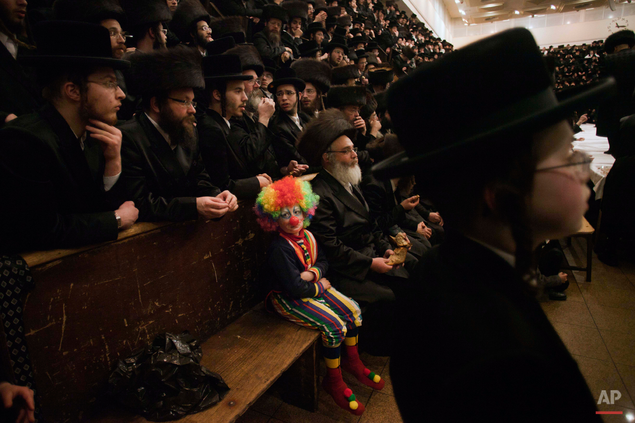 A child dressed in a clown costume, participates with other Ultra-Orthodox Jewish men in the Purim festival at a synagogue in Jerusalem, Thursday, March 8, 2012. The Jewish holiday of Purim celebrates the Jews' salvation from genocide in ancient Persia, as recounted in the Scroll of Esther. (AP Photo/Bernat Armangue)