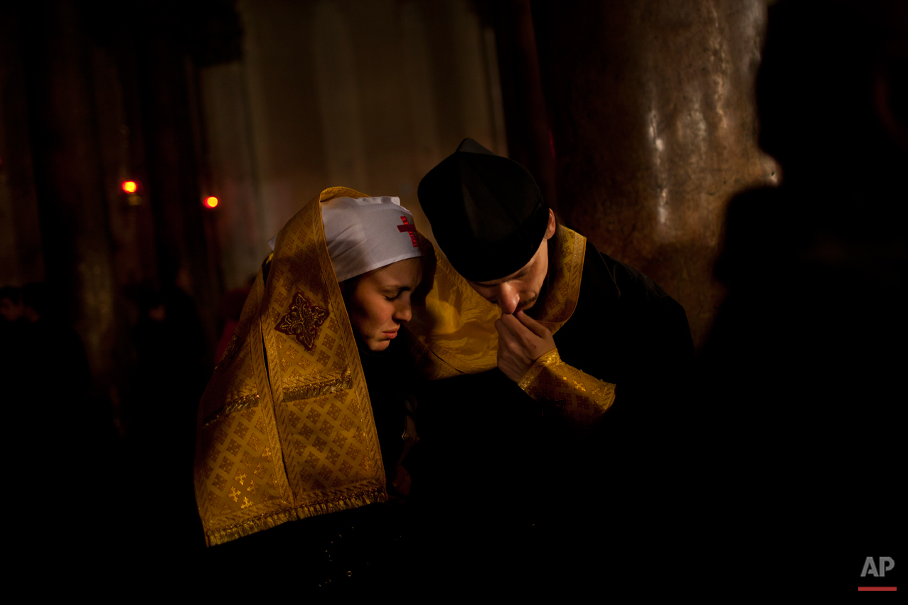 An Orthodox priest hears confession of a nun inside the Church of the Nativity, traditionally believed by Christians to be the birthplace of Jesus Christ, during Orthodox Christmas celebrations in the West Bank city of Bethlehem, late Friday, Jan. 6, 2012. (AP Photo/Bernat Armangue)
