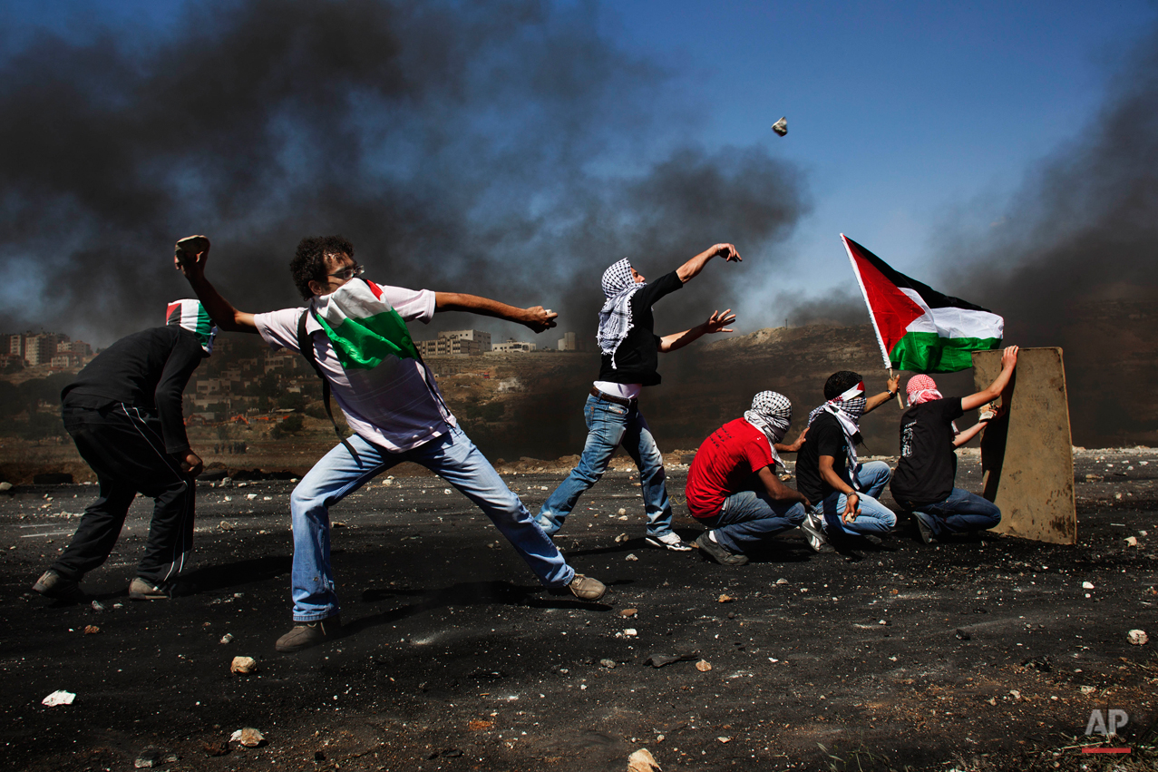 """Masked Palestinians hurl stones at Israeli troops, not seen, during clashes outside the Ofer military prison, near the West Bank city of Ramallah, Tuesday, May 15, 2012 during the 64th anniversary of """"Nakba"""", Arabic for catastrophe, the term used to mark the events leading to Israel's founding in 1948. Hundreds of thousands of Palestinians fled or were forced from their villages during the war over Israel's 1948 creation, an event they commemorate every year as their """"Nakba"""". (AP Photo/Bernat Armangue)"""