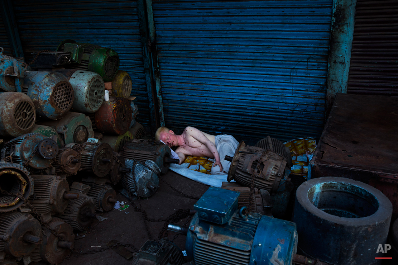 An albino man sleeps surrounded of piles of equipment in New Delhi, India, Tuesday, Aug. 26, 2014. Many laborers in the Indian capital have no permanent residence and are forced to sleep in the streets. (AP Photo/Bernat Armangue)