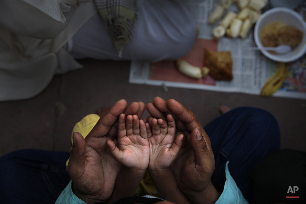 An Indian Muslim father holds the hands of his daughter in his palms and prays before  breaking fast on the first day of holy month Ramadan at the Jama Mosque in New Delhi, India, Monday, June 30, 2014. During this month the world's estimated 1.6 billion Muslims will abstain from food, drink and other pleasures from sunrise to sunset. (AP Photo /Manish Swarup)