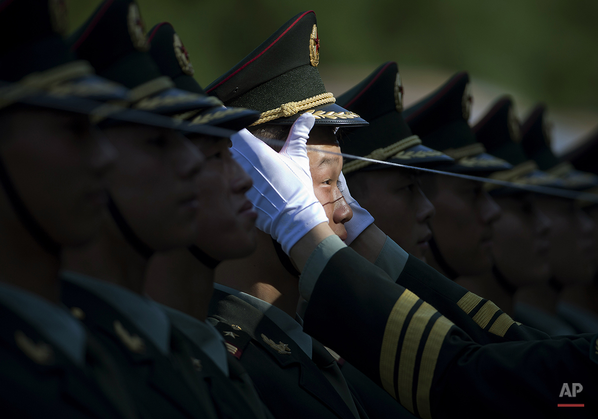 A Chinese People's Liberation Army soldier adjusts a hat of a member of a guard of honor as they prepare for a welcome ceremony for visiting Italian Prime Minister Matteo Renzi held outside the Great Hall of the People in Beijing, China Wednesday, June 11, 2014. (AP Photo/Andy Wong)