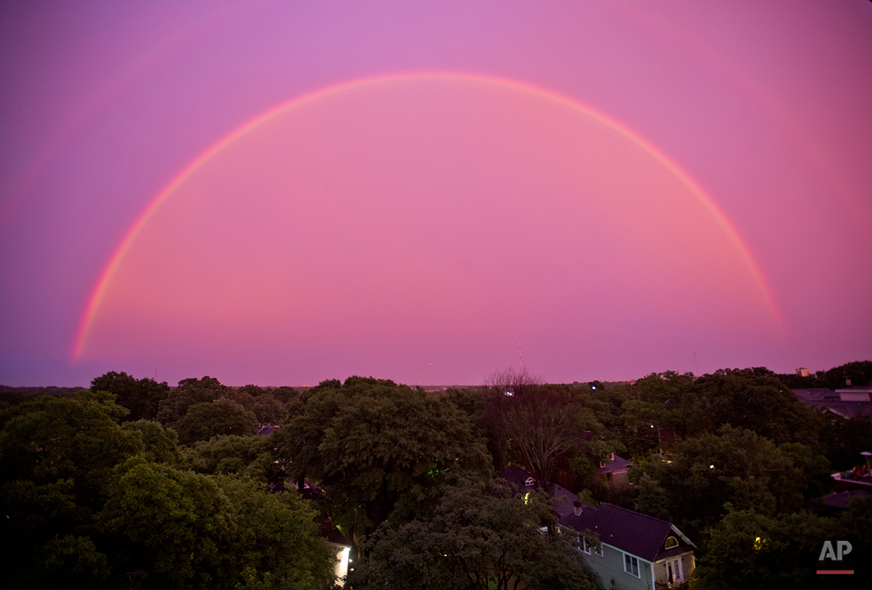 The sky turns pink as a rainbow appears at dusk after a thunderstorm, Thursday, June 5, 2014, in Atlanta. (AP Photo/David Goldman)