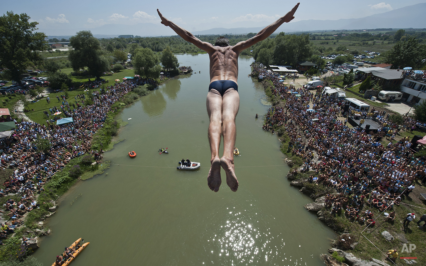 Spectators watch as a diver Sali Riza Grancina, winner of the competition, performs the winning jump from the Ura e Shenjte bridge during the traditional annual high diving competition, near the town of Gjakova, 100 kms south of Kosovo capital Pristina on Sunday, Aug. 10, 2014. Total of 27 divers from Kosovo competed diving 22 meters high bridge into the Drini i Bardhe river. (AP Photo/Visar Kryeziu)
