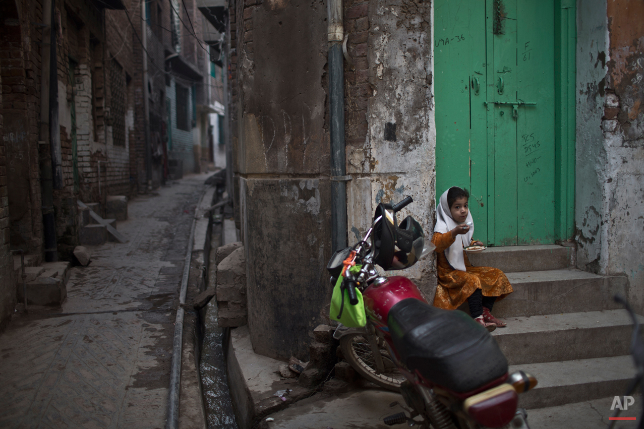 A girl, eats by the doorway of her home, near the house of Pakistani student Nasrullah Abdullah, 17, who was killed in last Tuesday's Taliban attack on a military-run school, in Peshawar, Pakistan, Thursday, Dec. 18, 2014. The Taliban massacre that killed more than 140 people, mostly children, at a military-run school in northwestern Pakistan left a scene of heart-wrenching devastation, pools of blood and young lives snuffed out as the nation mourned and mass funerals for the victims got underway. (AP Photo/Muhammed Muheisen)