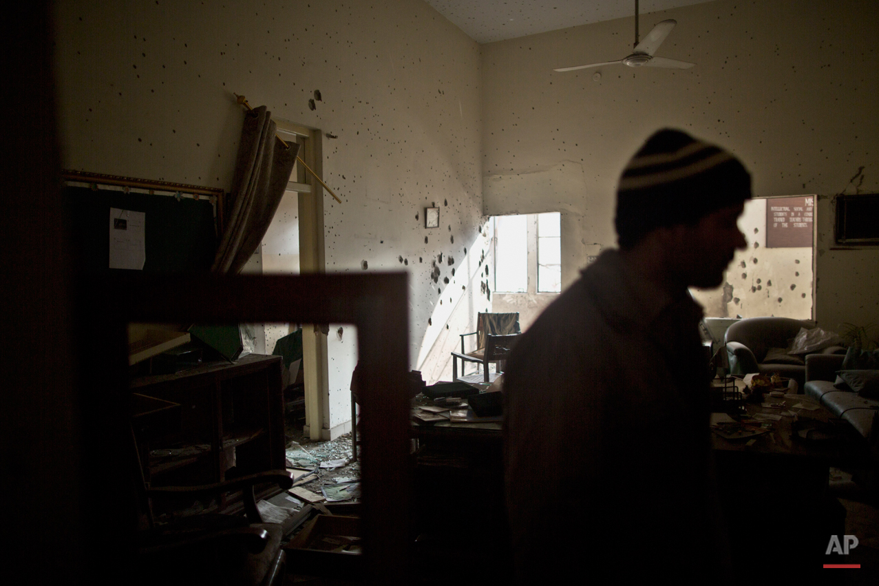 A Pakistani man checks the damage inside the room of headmaster Tahira Kazi, 58, who was killed in Tuesday's Taliban attack on a military-run school in Peshawar, Pakistan, Thursday, Dec. 18, 2014. The Taliban massacre that killed more than 140 people, mostly children, at the military-run school in northwestern Pakistan left a scene of heart-wrenching devastation, pools of blood and young lives snuffed out as the nation mourned and mass funerals for the victims got underway. (AP Photo/Muhammed Muheisen)