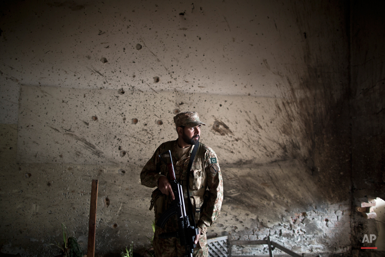 A Pakistani army officer, stands in front of a wall riddled with bullet marks, inside the Army Public School attacked last Tuesday by Taliban gunmen, in Peshawar, Pakistan, Thursday, Dec. 18, 2014. The Taliban massacre that killed more than 140 people, mostly children, at a military-run school in northwestern Pakistan left a scene of heart-wrenching devastation, pools of blood and young lives snuffed out as the nation mourned and mass funerals for the victims got underway. (AP Photo/Muhammed Muheisen)