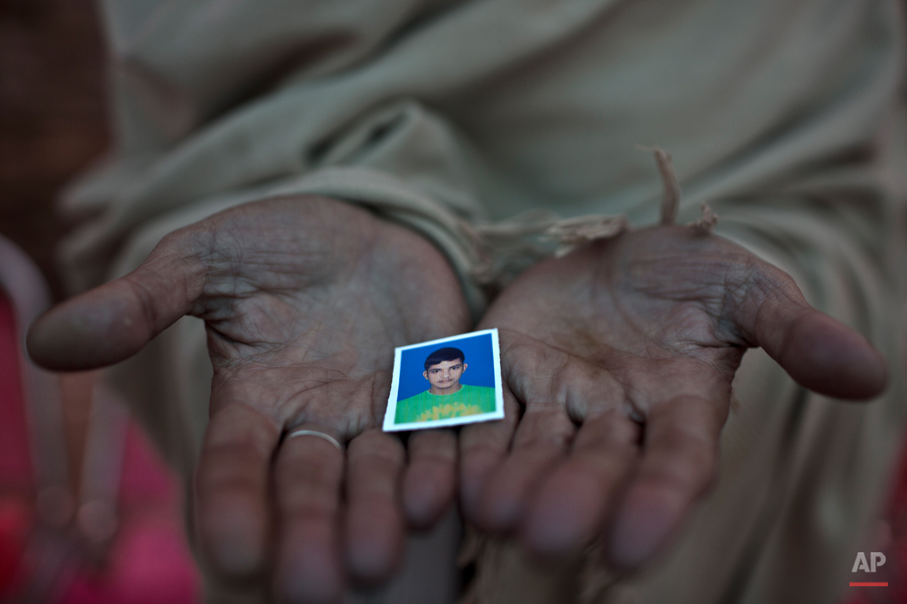 Pakistani Sayed Shah, shows a picture of his son Zulqarnain, 17, a student who was killed in  last Tuesday's Taliban attack on a military-run school, in Peshawar, Pakistan, Thursday, Dec. 18, 2014. The Taliban massacre that killed more than 140 people, mostly children, at a military-run school in northwestern Pakistan left a scene of heart-wrenching devastation, pools of blood and young lives snuffed out as the nation mourned and mass funerals for the victims got underway. (AP Photo/Muhammed Muheisen)