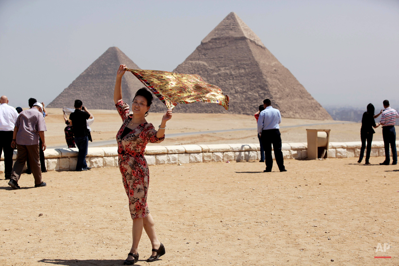 A tourist poses for a photographer, unseen, at the historical site of the Giza Pyramids, near Cairo, Egypt, Tuesday, Aug. 27, 2013. Tourism in Egypt has dropped following unrest surrounding the July 3 popularly backed military coup that ousted President Mohammed Morsi. (AP Photo/Jon Gambrell)