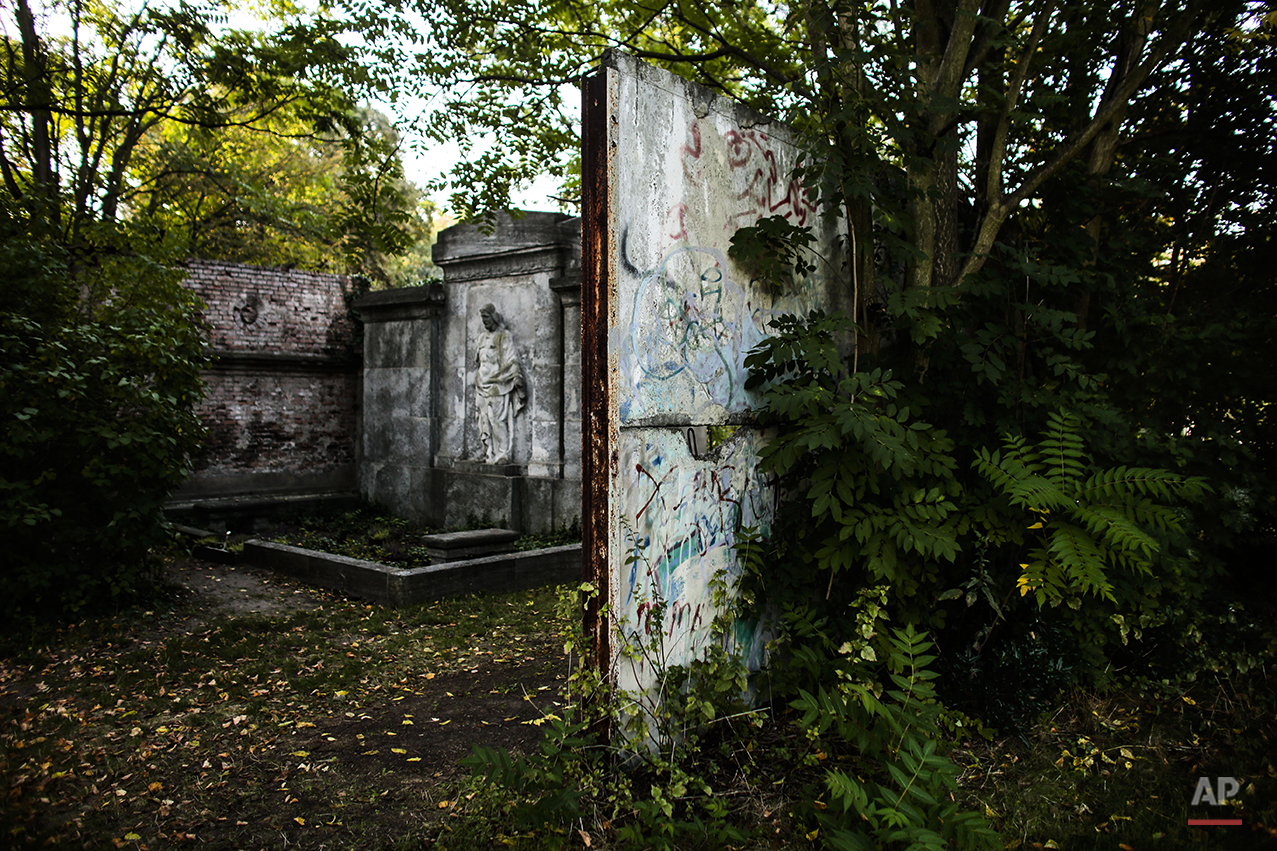 In this Sept. 17, 2014 photo a few meters long part of the former Berlin Wall sits on the cemetery of the French community in Berlin. On Nov. 9, 2014, Germany celebrate the 25th anniversary of the fall of the wall on Nov. 9, 1989. After 25 years only a few remains of the wall remind of the about 160 kilometers (about 100 miles) long border which surrounded the west part of Berlin. (AP Photo/Markus Schreiber)