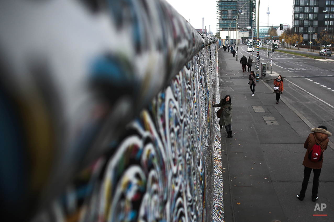 In this Nov. 4, 2014 photo tourists walk alongside of the painted East Side Gallery in Berlin, the largest part of original remains of the Berlin Wall. On Nov. 9, 2014, Germany celebrate the 25th anniversary of the fall of the wall on Nov. 9, 1989. After 25 years only a few remains of the wall remind of the about 160 kilometers (about 100 miles) long border which surrounded the west part of Berlin. (AP Photo/Markus Schreiber)
