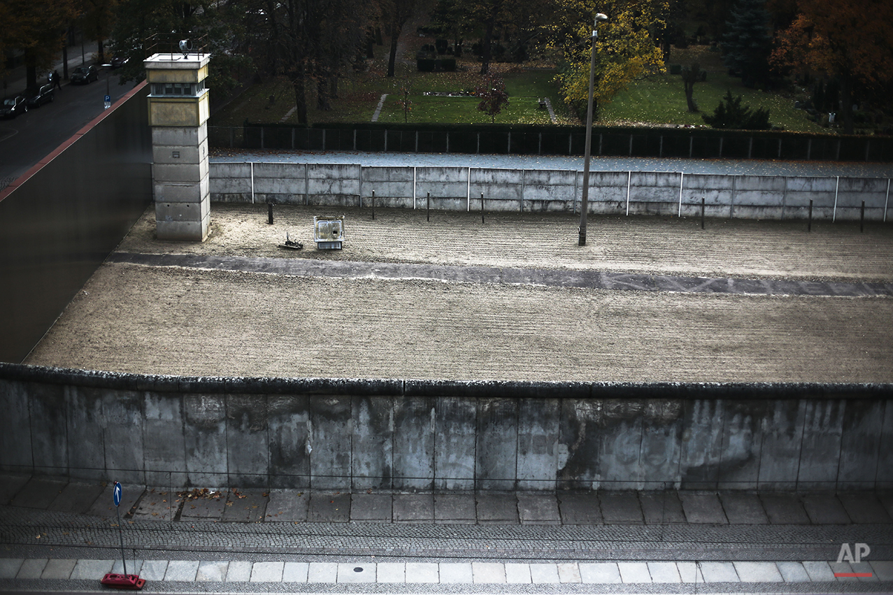 The Nov. 4, 2014 photo shows the the remembrance site for the Berlin Wall at Bernauer Strasse in Berlin.  On Nov. 9, 2014, Germany celebrate the 25th anniversary of the fall of the wall and the end of the Iron Curtain on Nov. 9, 1989. After 25 years only a few remains of the wall remind of the about 160 kilometers (about 100 miles) long border which surrounded the west part of Berlin. At the remembrance site Bernauer Strasse some hundred meters of original wall parts still exist. The barricade consisted of two walls and a so-called 'death strip' in between where dogs patrolled and East-German border guards where allowed to use their weapons to stop people who tried to escape to the West.  (AP Photo/Markus Schreiber)