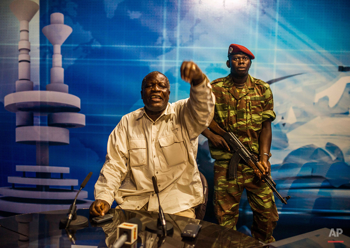 Burkina Faso army Gen. Kwame Lougue, center, with a armed guard at the state television studios, after he entered without speaking to journalists who were waiting  for a announcement by opposition politician Saran Sereme, shorty after gun shots were heard outside the building in Ouagadougou, Burkina Faso, Sunday, Nov. 2, 2014.Gunfire erupted outside the headquarters of state television in Burkina Faso on Sunday as an opposition politician tried to announce she was in control of the West Africa country plunged into chaos days earlier when the army took power after the president of 27 years was forced out. (AP Photo/Theo Renaut)