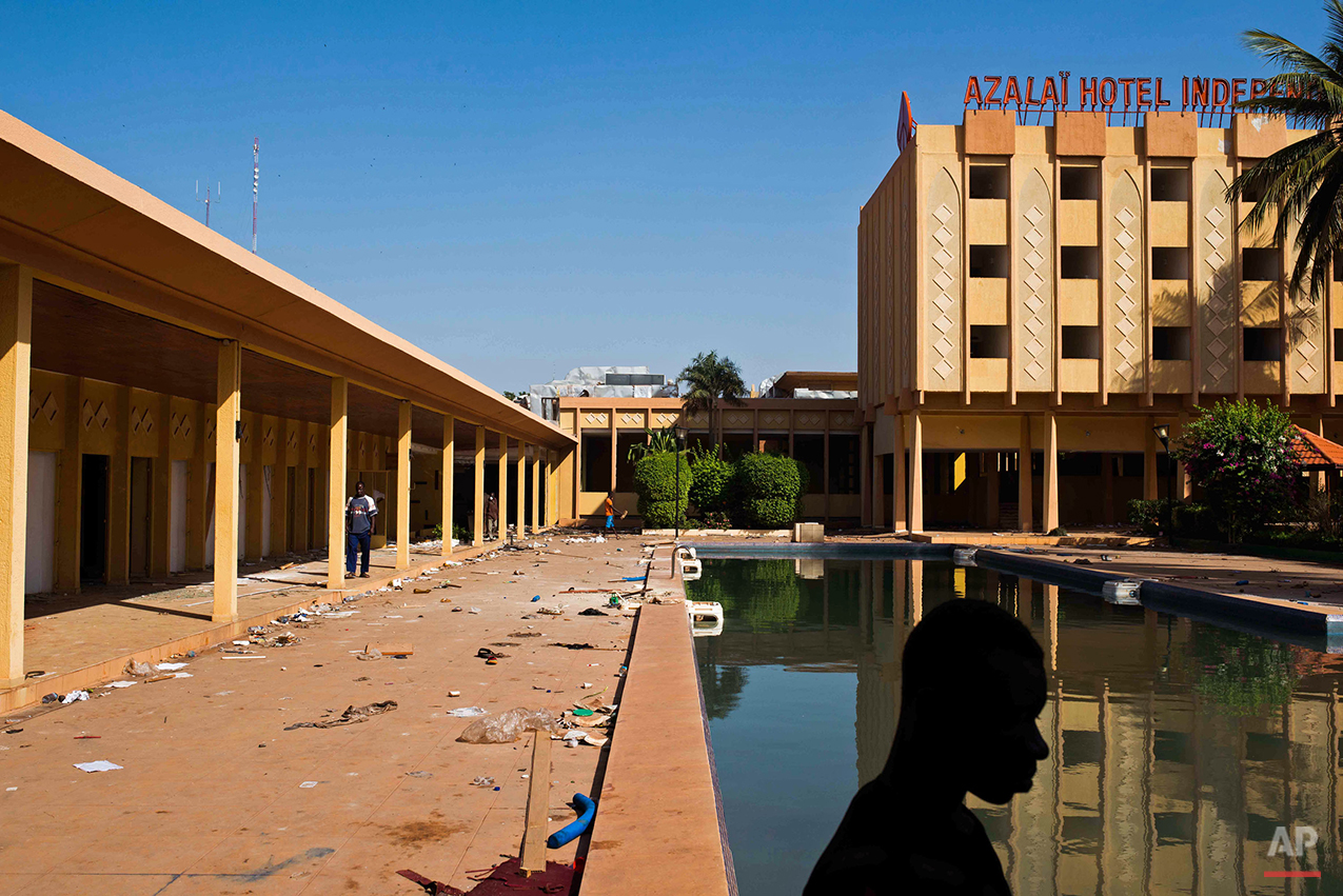 People walk near the Azalai Hotel swimming pool after the hotel was looted by anti-government protestors days before in Ouagadougou, Burkina Faso, Saturday, Nov. 1, 2014. Burkina Faso's former president fled to neighboring Ivory Coast with his family after violent protests drove him from power after 27 years in office, Ivory Coast said Saturday, as a largely unknown military colonel said he had taken the helm. (AP Photo/Theo Renaut)