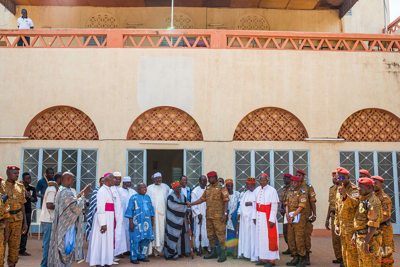 Burkina Faso Lt. Col. Issac Yacouba Zida, center, shakes the hand of  Mossi emperor Mogho Naaba, leader of the Mossi tribe  and the largest ethnicity in the country, in the city of Ouagadougou, Burkina Faso, Tuesday, Nov. 4, 2014.  International envoys tried Tuesday to resolve Burkina Faso's political crisis, with the specter of a power vacuum looming after the country's longtime president fled last week. (AP Photo/Theo Renaut)