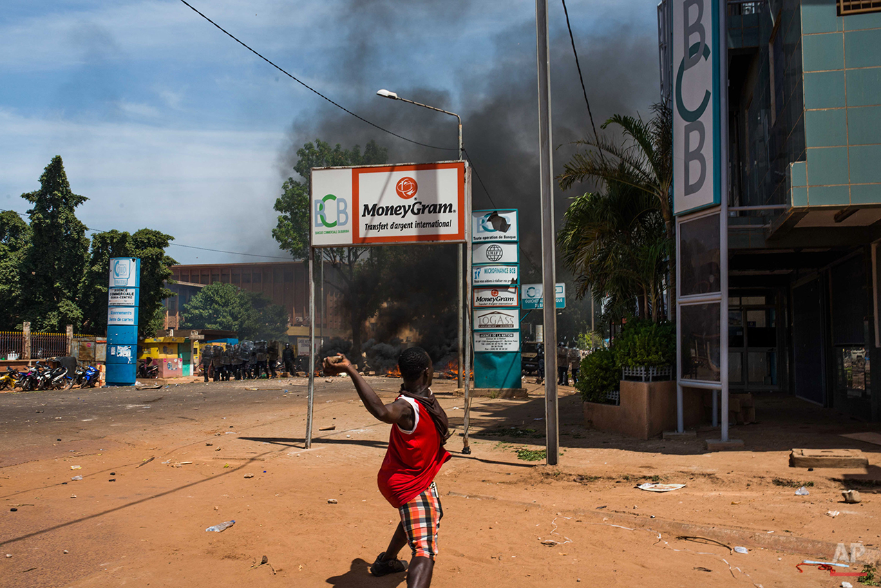 A protestor throws a rock at a line of police officers as he and others demonstrate against Burkina Faso's president seeking another term in office, in Ouagadougou, Burkina Faso, Tuesday, Oct. 28, 2014. Police used tear gas on Tuesday to disperse an opposition protest in Burkina Faso's capital, as tensions increase ahead of a vote this week on whether the country's longtime president can seek another term.  (AP Photo/Theo Renaut)
