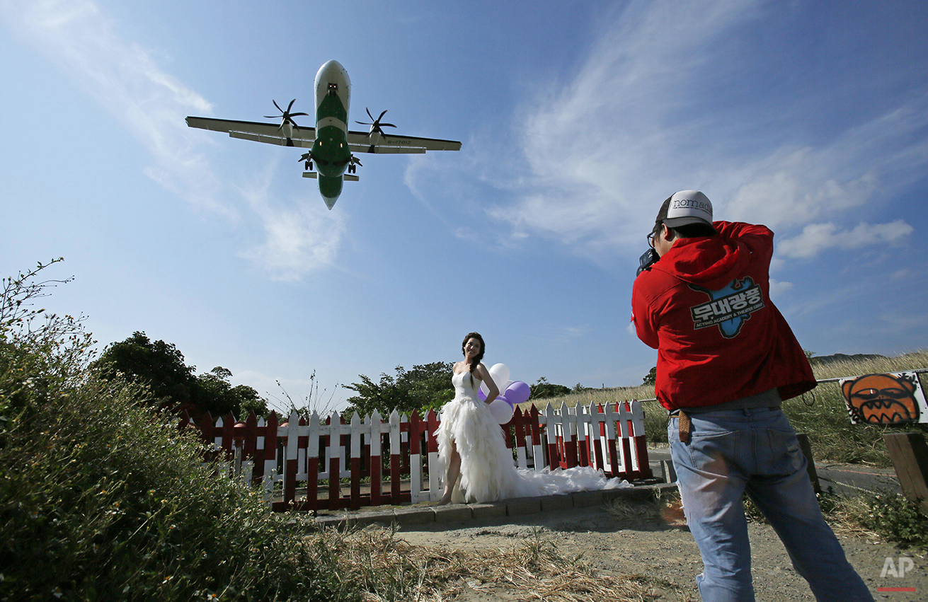 A bride has her wedding photos taken under the flight path at Songshan airport in Taipei, Taiwan, Thursday, Oct. 30, 2014.  (AP Photo/Wally Santana)