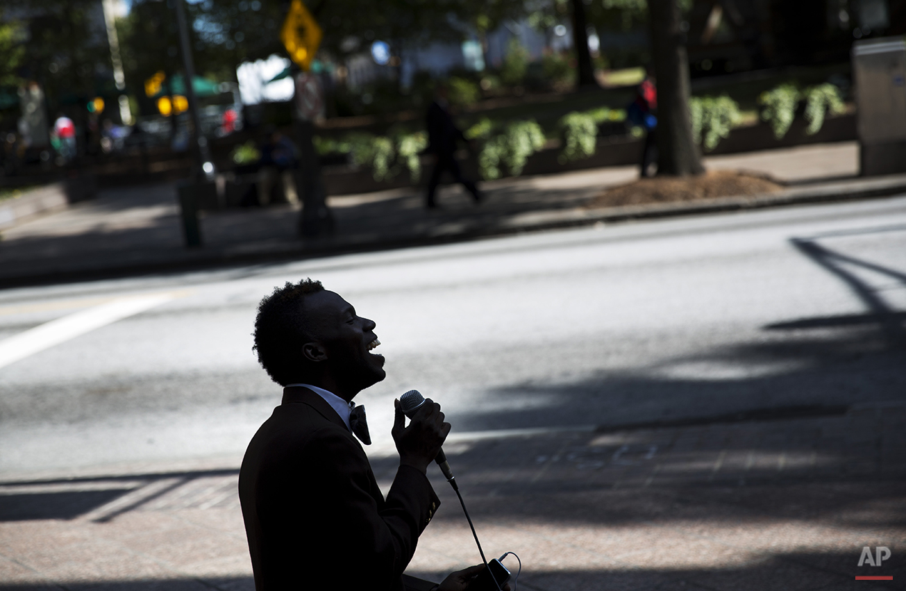 "Nathaniel Marcqiese Rainey, 28, sits along Peachtree Street while singing Ray Charles' ""Georgia on My Mind,"" Thursday, Oct. 23, 2014, in Atlanta. (AP Photo/David Goldman)"