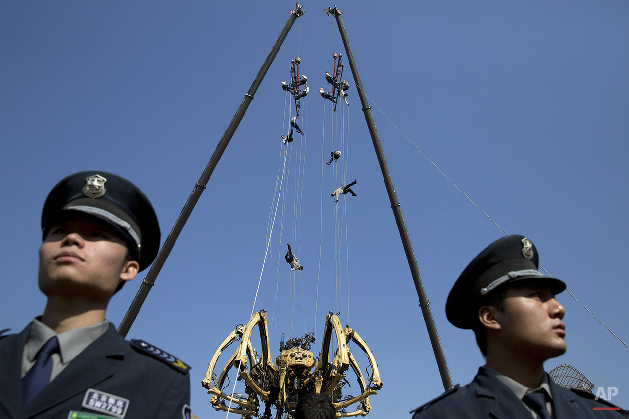 Performers rappel down to the French production company La Machine's mechanical spider, also known as La Princesse, during a show held in front of the Bird's Nest Stadium in Beijing Friday, Oct. 17, 2014. (AP Photo/Ng Han Guan)