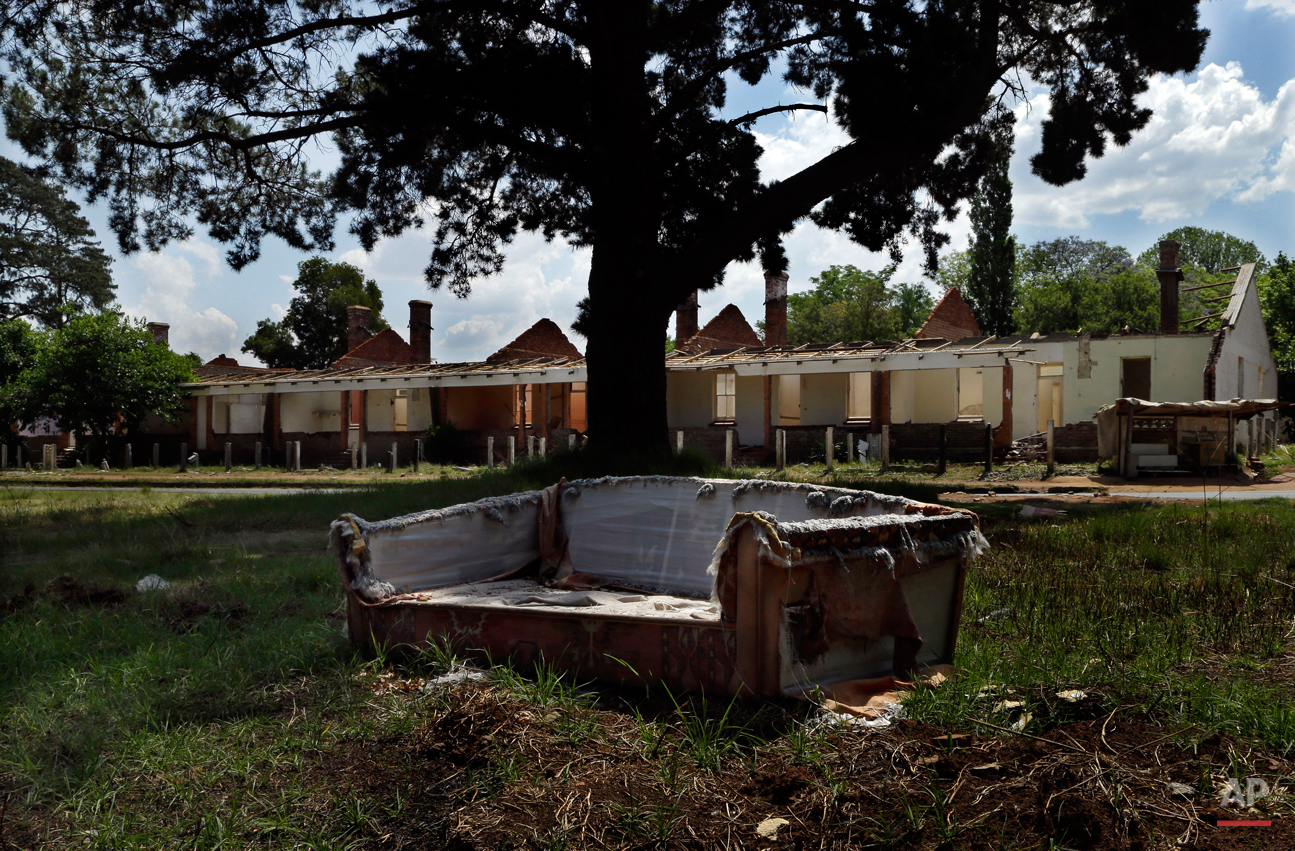 This Oct. 24, 2014, photo shows a broken coach placed next a road nearby abandoned houses at Durban Deep mine residential area in Roodepoort, west of Johannesburg, South Africa. The once sought-after mining facility at Durban Deep now is in a crime-ridden state. The buildings have been stripped of everything valuable and sold for cash. (AP Photo/Themba Hadebe)